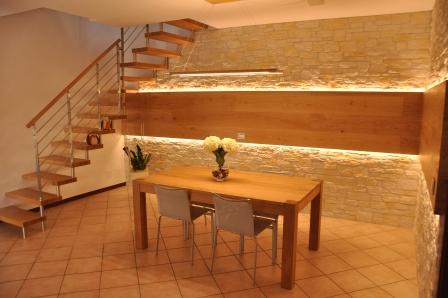 Visione d'insieme di scala, tavolo e parete in legno di Artigiana Arredamenti a Verona